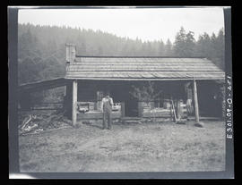 Oak grove project, man standing in front of cabin