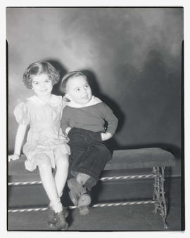 Dolores Mitchell and unidentified young boy sitting on bench