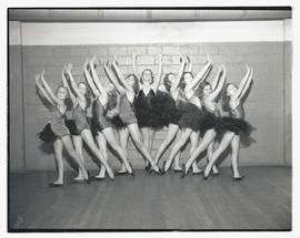 Ballet dancers in costume, posing with arms raised