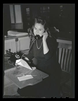 Office worker speaking on telephone during swing shift, Albina Engine & Machine Works, Portland