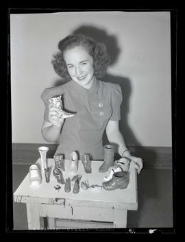 1942 Portland Rose Festival Princess Jean Grashorn posing with shoe collectibles