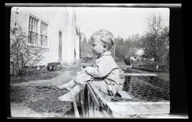 Young boy seated on chicken coop?