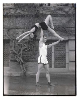 Pair of acrobats, one holding the other overhead