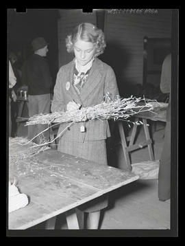 Unidentified 4-H member holding bundle of dried plants at Pacific International Livestock Exposition