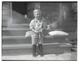 Unidentified young boy in front of stairs, full-length portrait