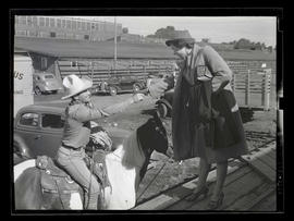 Woman and cowboy shaking hands, probably at Pacific International Livestock Exposition