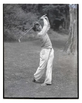 Young golfer posing with golf club
