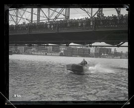 Man driving speedboat under Morrison Bridge, Portland, as crowd watches