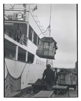 Pallet of crates being hoisted onto ship