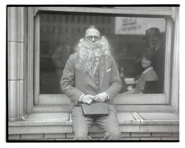 Unidentified man wearing fake beard and holding case
