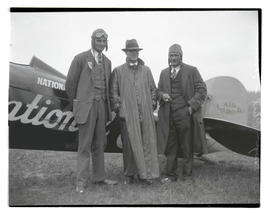 "Charles W. ""Speed"" Holman, Phil, and E. E. Ballough next to airplane"