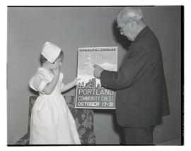 Man showing Portland Community Chest poster to child in nurse costume