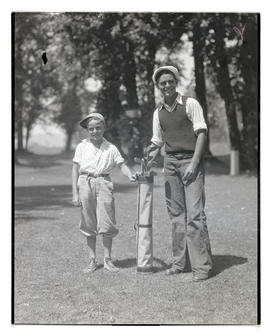 Two boys posing with bag of golf clubs