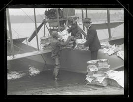 David H. Smith and two unidentified men loading seaplane for Oregon Journal delivery