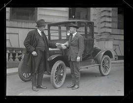 George L. Baker and Warford standing with car and holding document