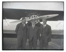 Anthony Mackiewicz, Charles Dickinson, and E. E. Ballough in front of airplane