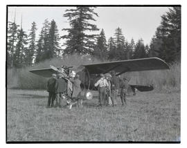 Group of people in field with airplane