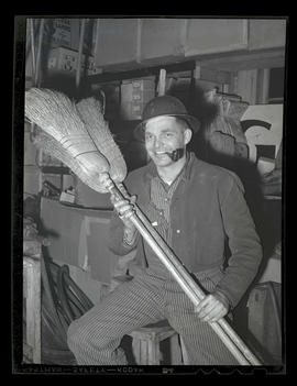 Worker holding brooms, Albina Engine & Machine Works, Portland