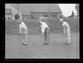 Three unidentified golfers posing with clubs