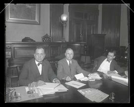Three unidentified men at table in courtroom