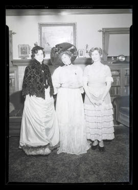 Three costumed women in sitting room