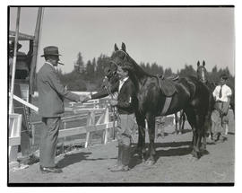 Boy with horse and trophy, shaking man's hand