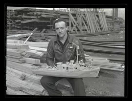 Worker holding model ship, Albina Engine & Machine Works, Portland