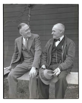 Two unidentified men sitting on railing, probably at Pacific International Livestock Exposition