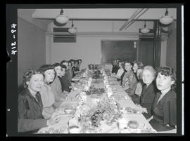 Women at long dining table in office