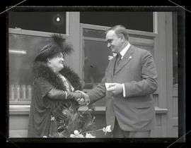George L. Baker shaking hands with unidentified woman
