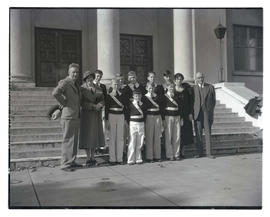Boys in matching shirts and belts with four adults outside building