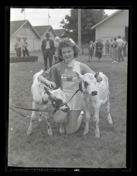 Young woman posing with two calves