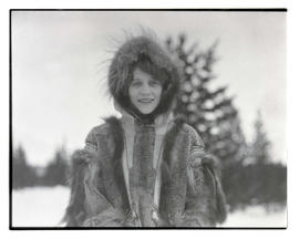 Woman outdoors on winter day, wearing fur coat