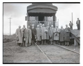 Group of men in front of train car, possibly at livestock show
