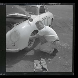 Man working on car at auto races in Tillamook, June 1955