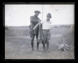 Unidentified man helping unidentified woman put on jacket