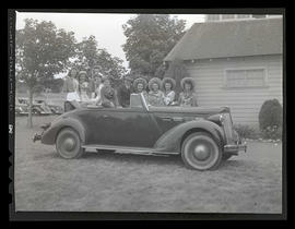 People posing with car, possibly at county fair