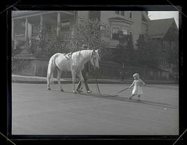 Oswald West's daughter Jean leading horse down neighborhood street