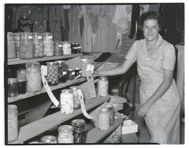 Young woman posing with display of canned food
