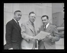 Sandy, Donaugh, and unidentified man holding Veterans of Foreign Wars document