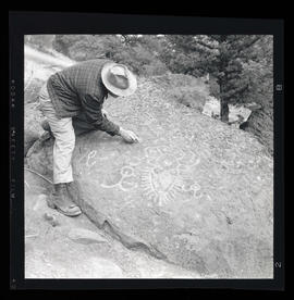 Man looking at Cove Palisades State Park petroglyphs