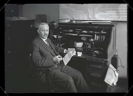 Unidentified man sitting at desk and holding letter