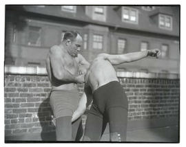 Two men wrestling on rooftop or balcony