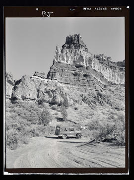 Vehicle and dirt road with Ship Rock at Cove Palisades State Park area