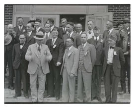 Group of unidentified men on steps outside building