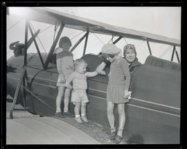Three children on airplane wing next to woman in cockpit