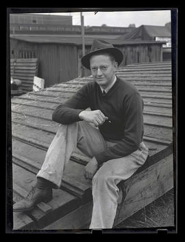 Unidentified man sitting on ramp, probably at Pacific International Livestock Exposition
