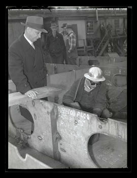 G. H. van der Stoop watching workers lay keel for Dutch cargo ship, Albina Engine & Machine W...