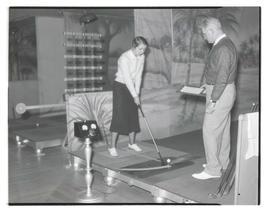Student using golf training device as instructor watches