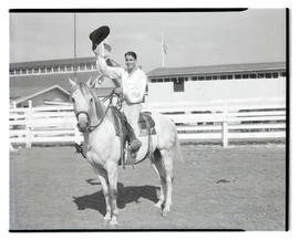Man on horseback, doffing his hat
